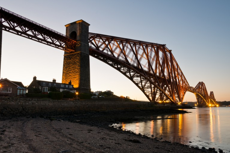 A photograph of a red metal bridge lit up from below, with light reflecting in the water.
