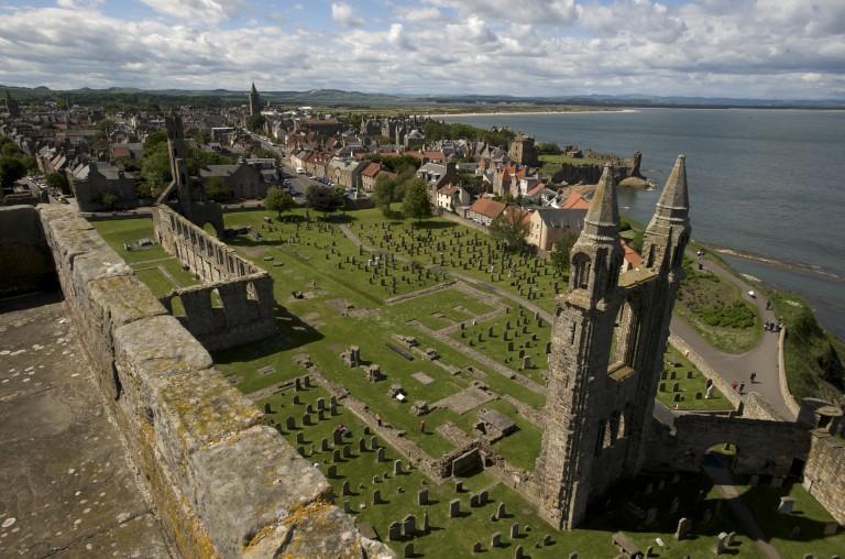 view looking down on a ruined section of a cathedral tower with gravestones and green grass, and in the distance houses and the sea