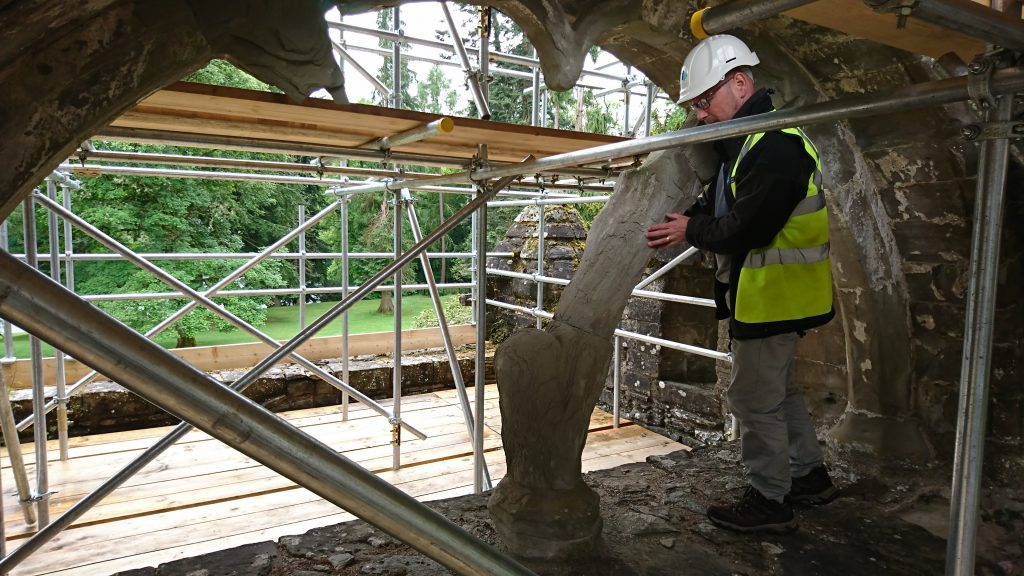 man in hi-vis vest and hard hat stands by scaffold in an old arched window examining an ancient fragment of stone
