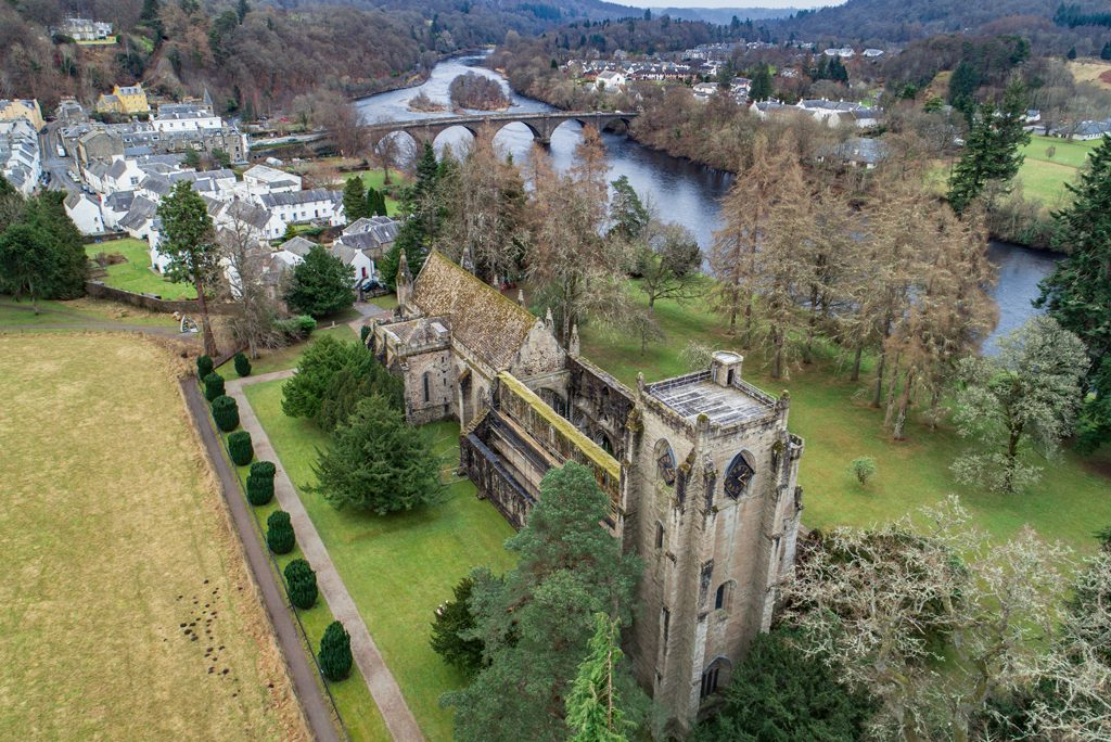 aerial view of Dunkeld Cathedral, a roofless church building lined with trees, with a river and bridge in the background