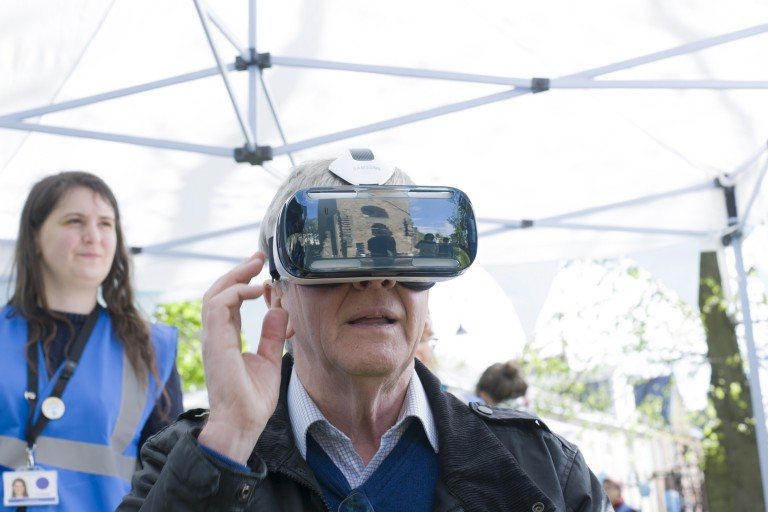 head and shoulders of elderly man wearing a virtual reality headset, looking fascinated by what he can see virtually. A medieval tower is reflected in the surface of the headset