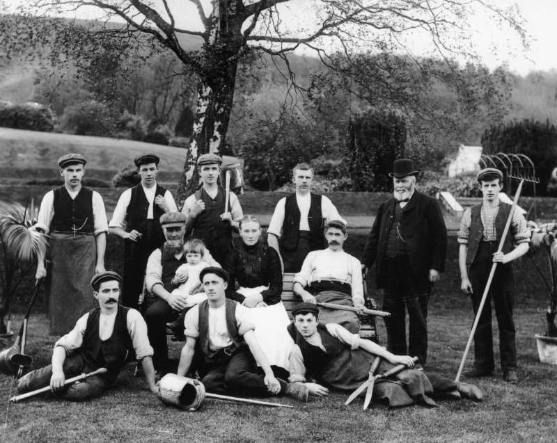 black and white image of a group of men seated and standing in gardens, holding watering cans, shears, rakes and other gardening implements