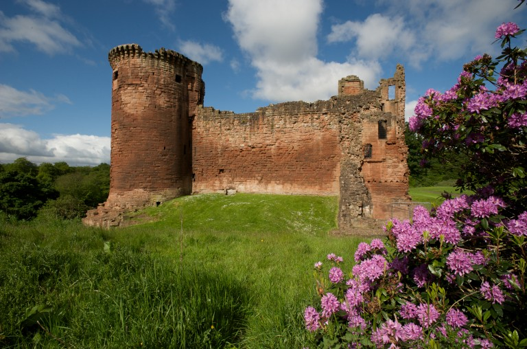 red stone castle with a round tower on a green verge with blue sky above and pink flowers in front