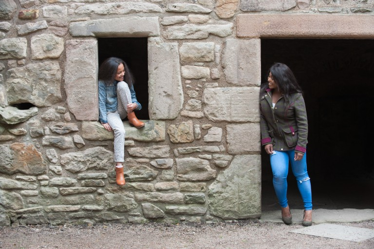 girl climbs through empty space where window might once have been in an old wall whilst her mum looks on from a doorway in the same wall
