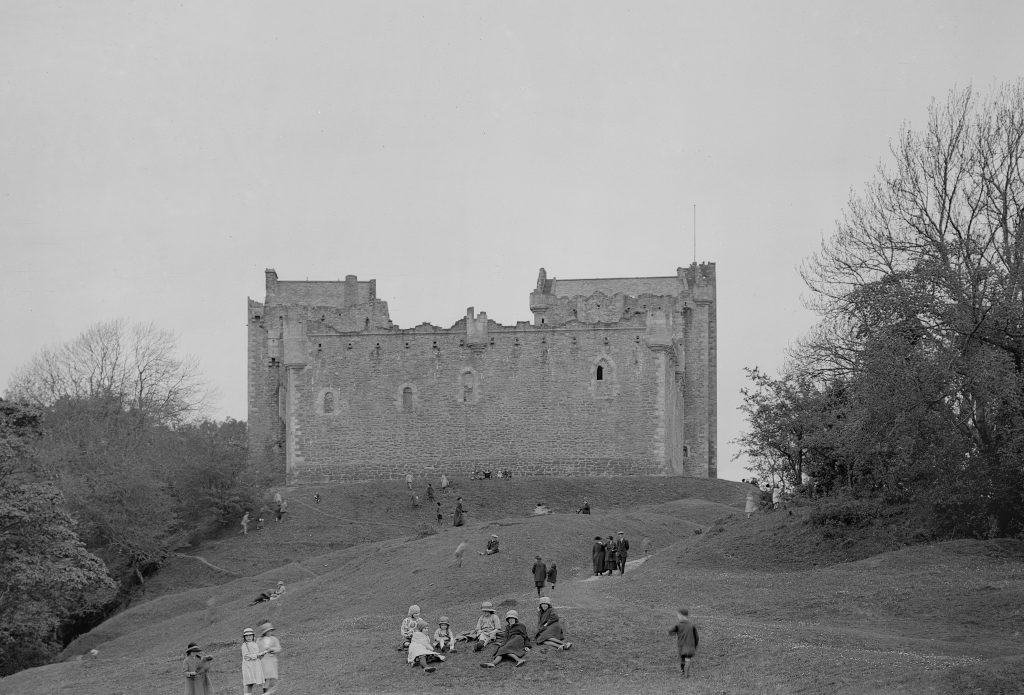 black and white image of castle wall with visitors sitting on verge in front of it