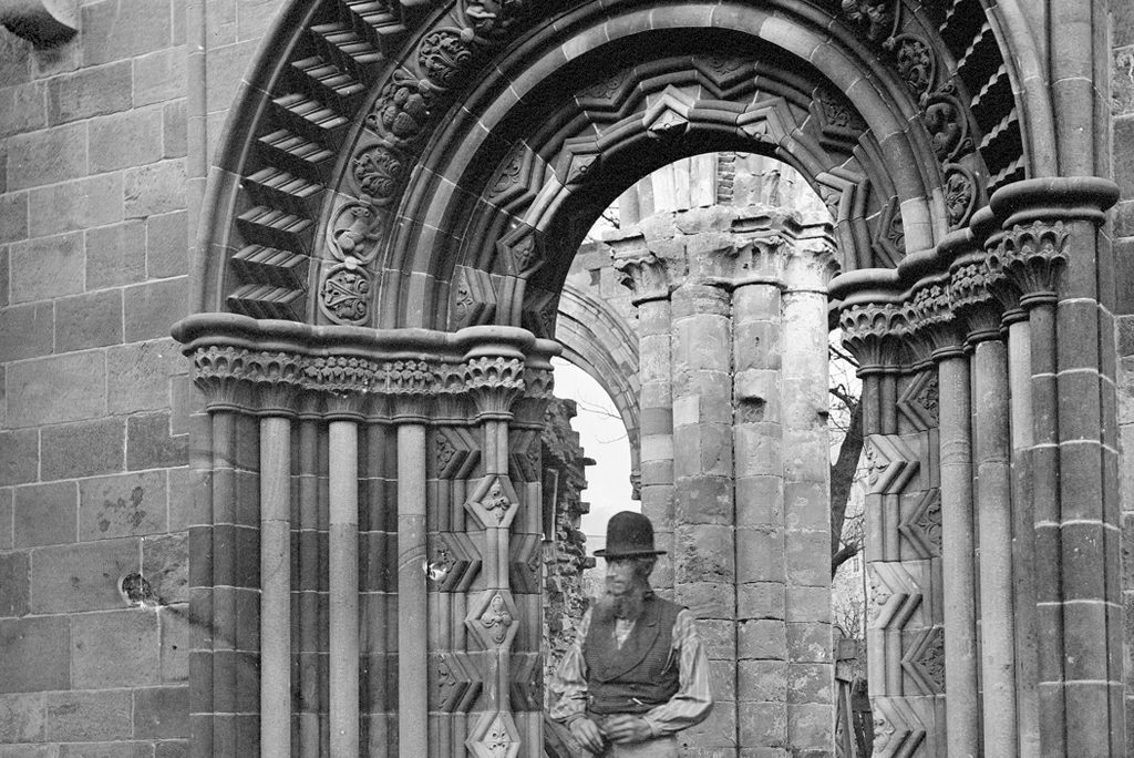 black and white picture of a bearded man wearing a bowler hat and a waistcoat standing under an archway