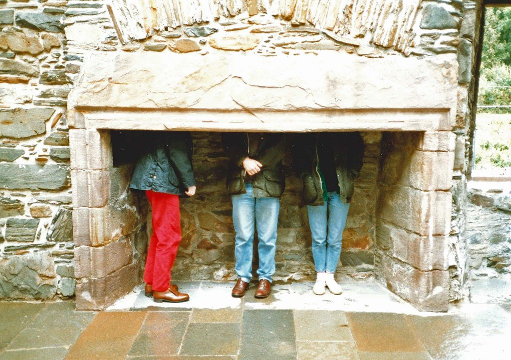 old fireplace with three people inside with only their legs visible