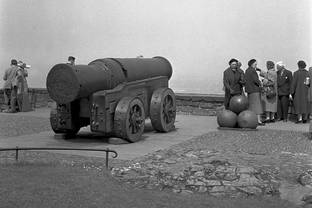 black and white image of an old cannon on wheeled carriage, pointed away from the camera as tourists stand to the right beside a pile of cannon balls