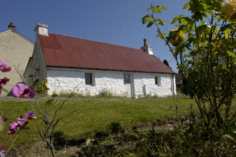 small white cottage with a red roof
