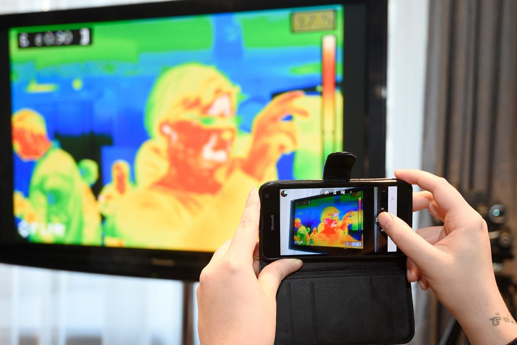 hands holding phone to take picture of screen showing orange thermal image of a woman with a ponytail