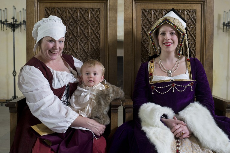 two women in historic costumes sit on wooden thrones, the woman on the left holds a small child with blonde hair, they are smiling for the camera