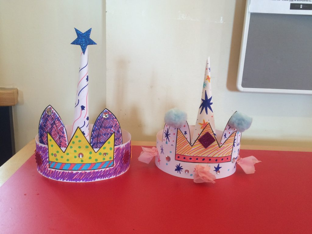 two paper crowns with unicorn horns in the middle