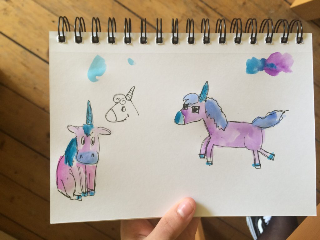 page in a sketchbook showing different sketches of a unicorn