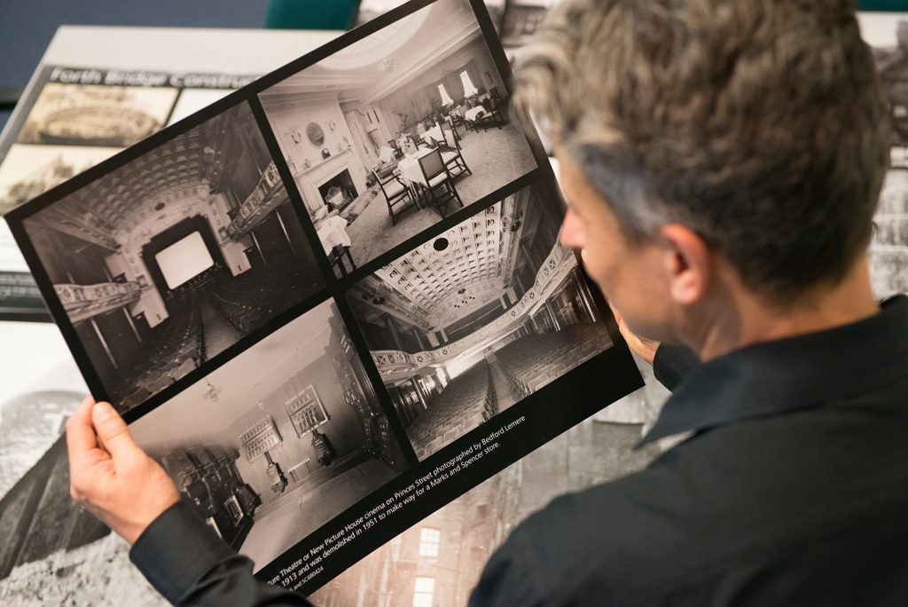 view of man inspecting a black and white negative with four views inside a historic building