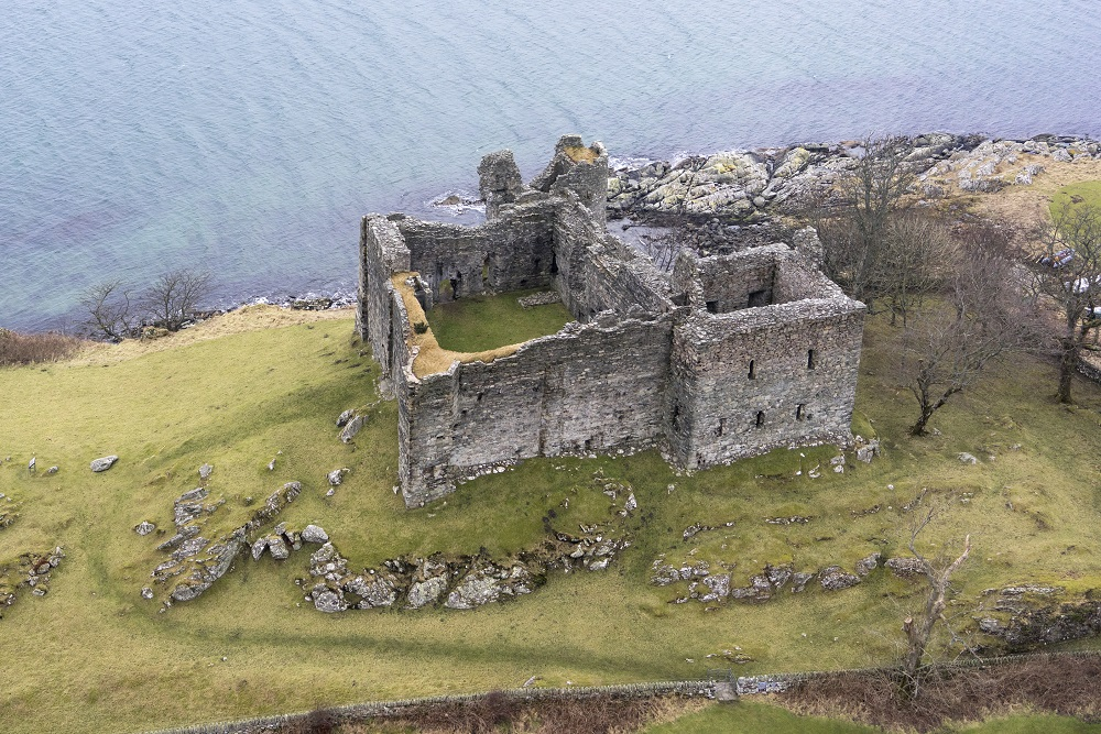 an aerial view of the shell of a grey stone castle on a green hill by a body of water