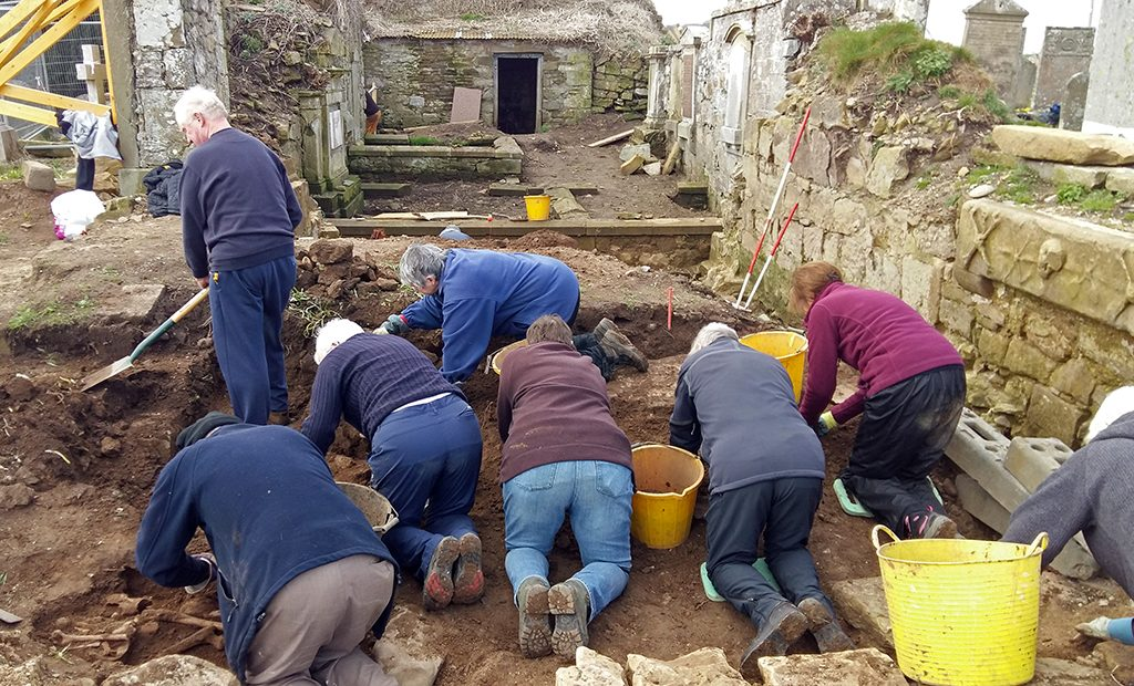 people on their hands and knees in a trench digging up soil to uncover archaeology