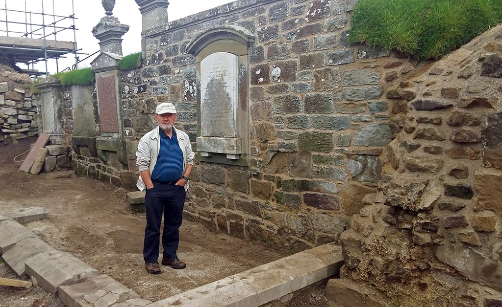man stands in front of recently repaired wall