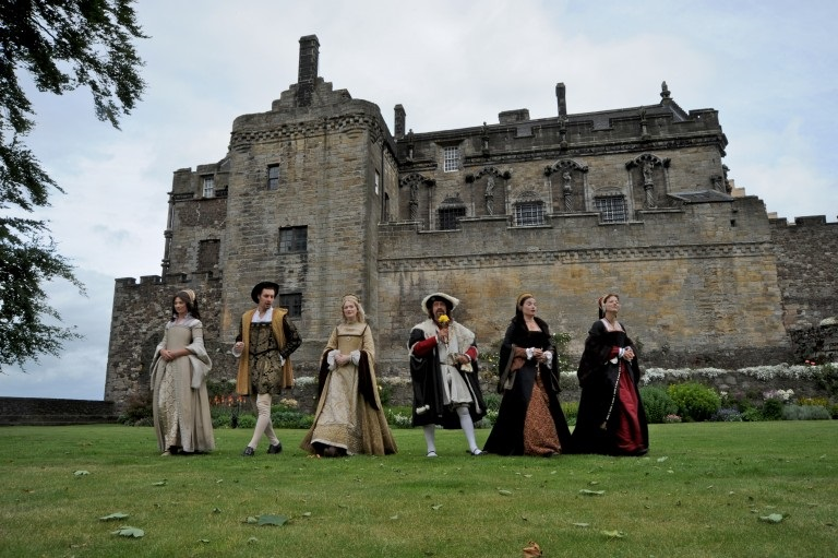 row of people in renaissance costume walking towards the camera with a castle behind them