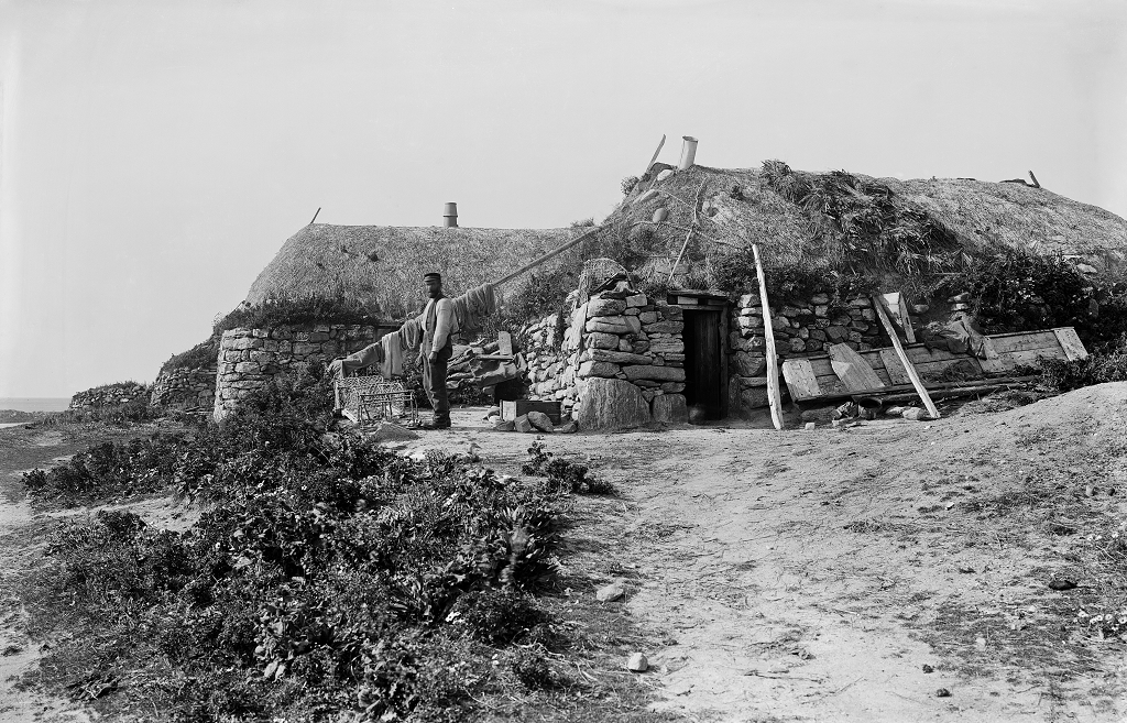 black and white photo of thatched blackhouses with man standing outside
