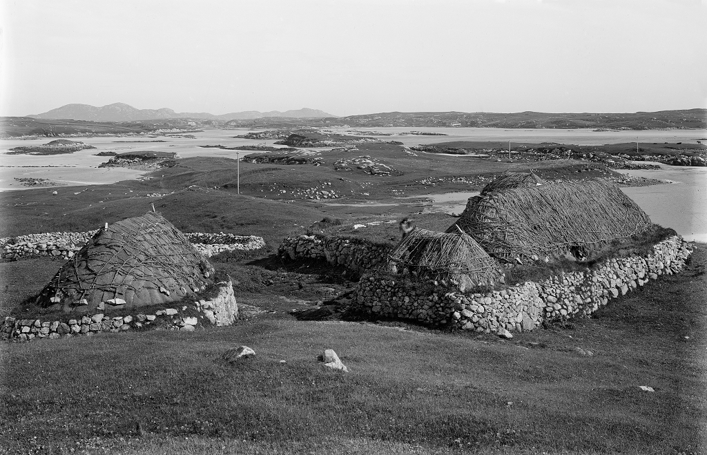 black and white photograph of thatched buildings on a remote island