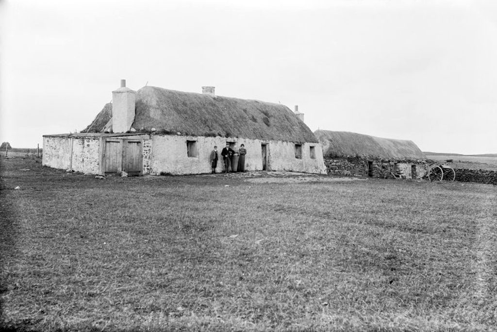 black and white photo showing four people standing outside the door of thatched inn with additional buildings to the right