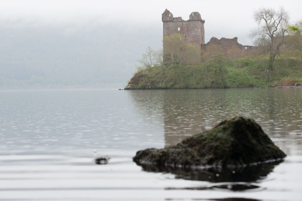 Image of castle ruins on the banks of a misty loch