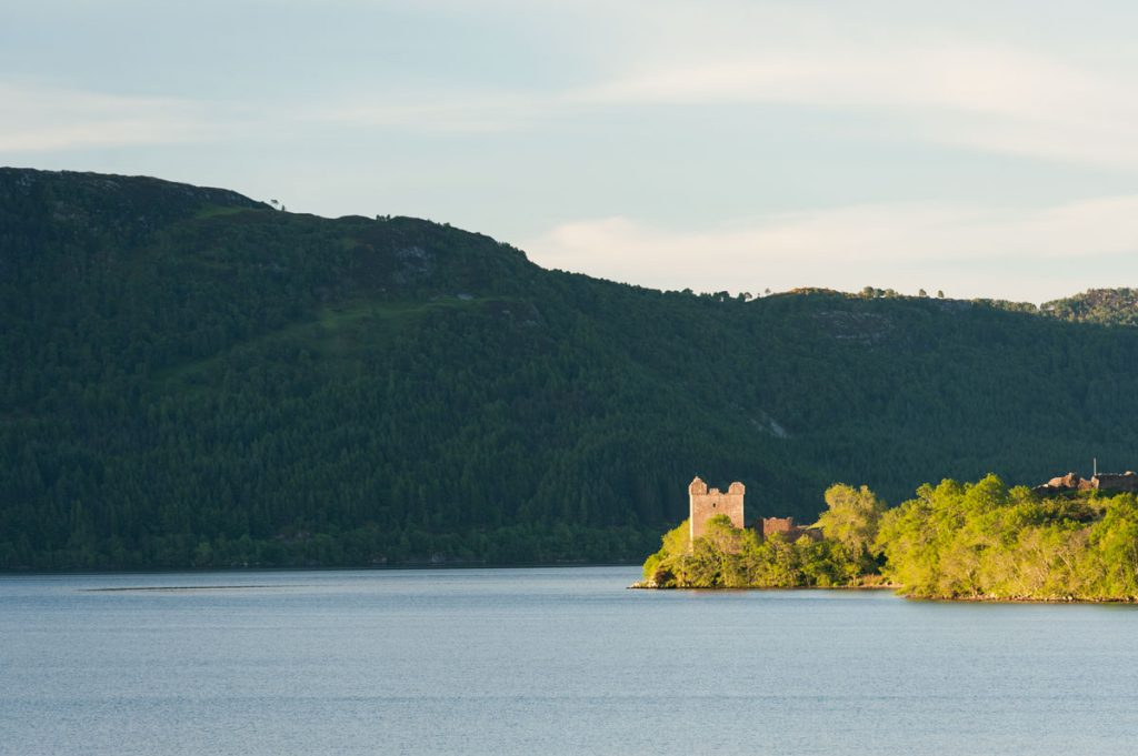 A castle sits on the banks of a loch in the sun