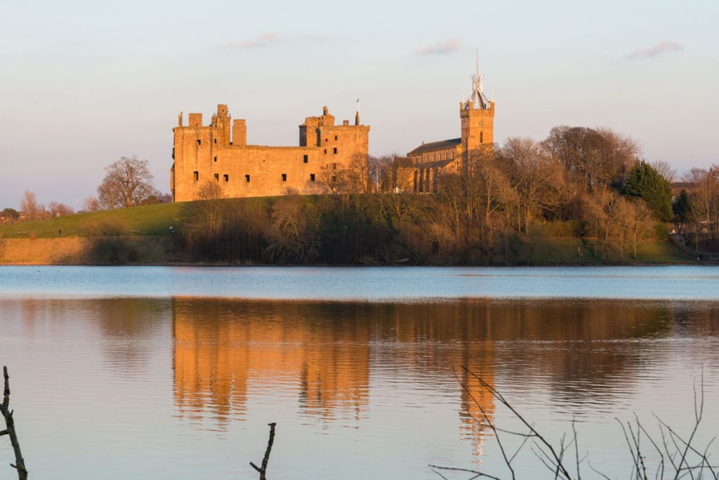 Image of an ancient palace on the banks of a loch at sunset