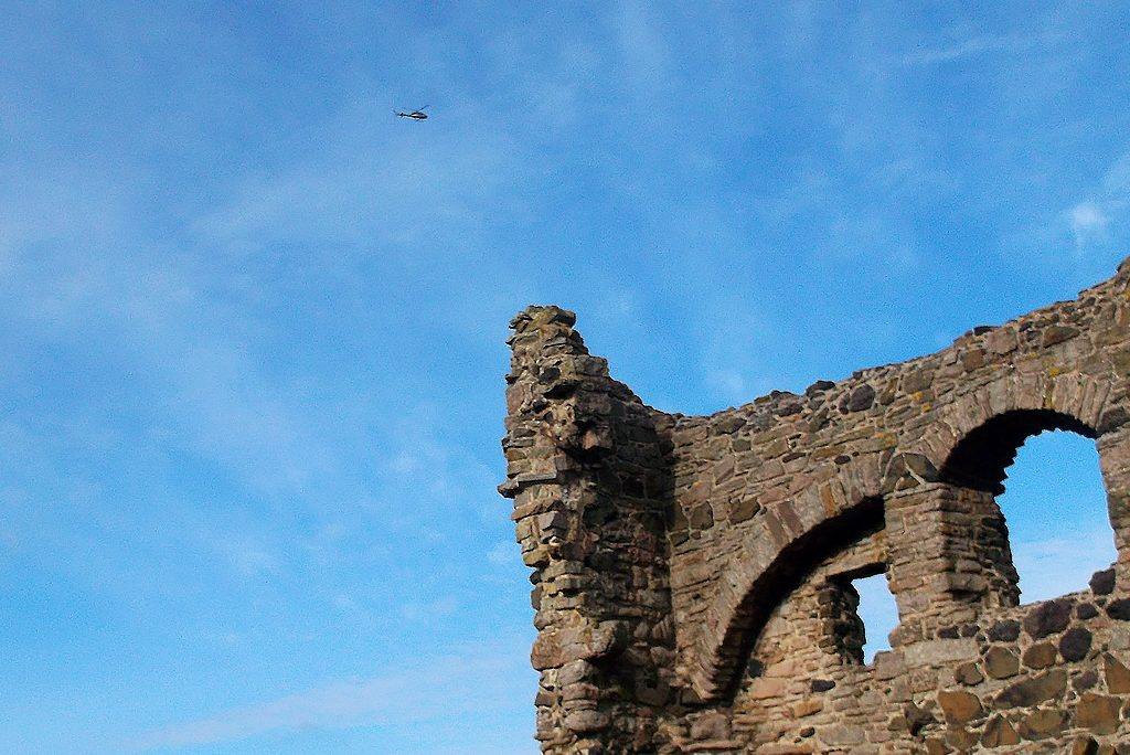 blue sky above the corner of a ruined building with a helicopter flying overhead