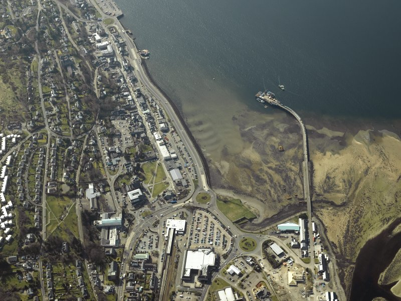 aerial view showing coast line with lots of buildings including a railway depot, church, pier and hospital,