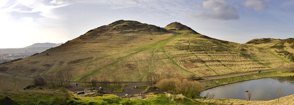 sloping green hill with ridges cut into the side, once used for growing crops