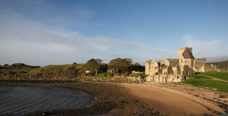 sandy bay with ruined abbey in the background beside it