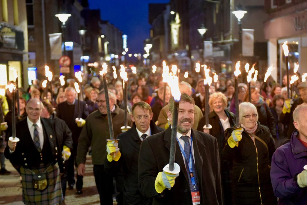 crowds of smiling people walk along a street bearing torches