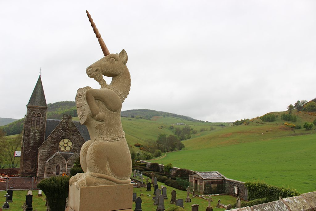 carved unicorn on a roof with church and hills in the background