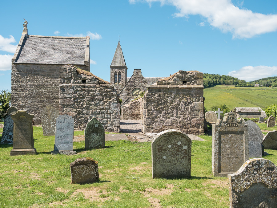 gravestones in front of a ruined church with a tower in the distance behind them