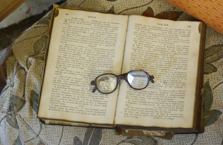 old book sitting open with a pair of glasses on top
