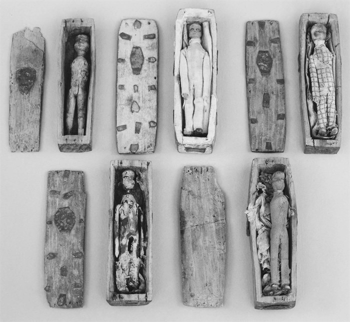 five miniature coffins with remains of dolls inside