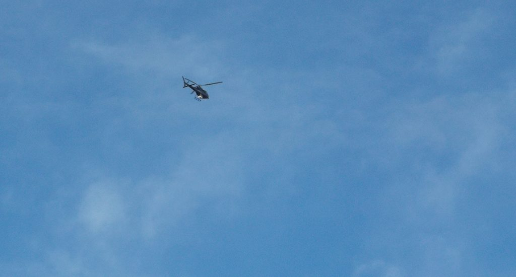 blue sky with a helicopter visible high above