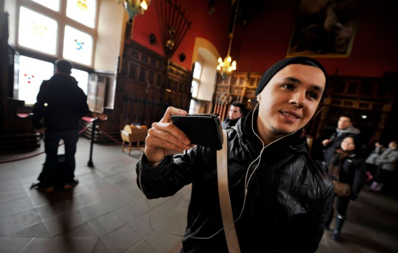Image of a young person visiting Edinburgh Castle taking photos with his smartphone
