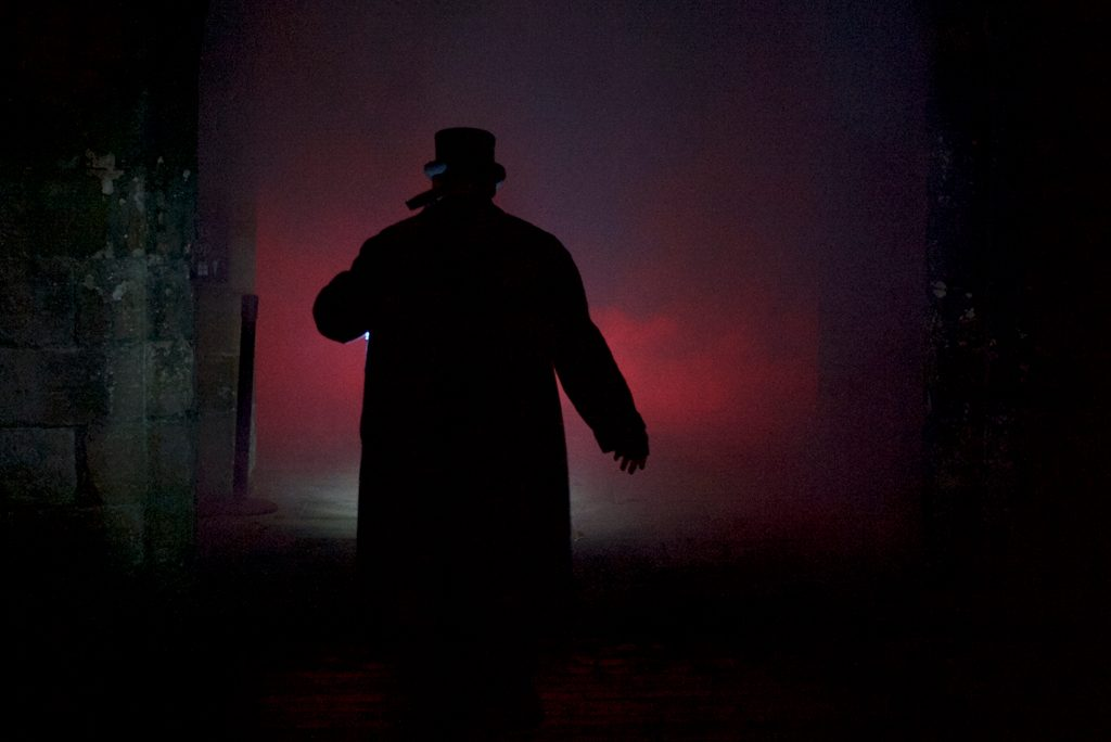 silhouette of a man walking into the night