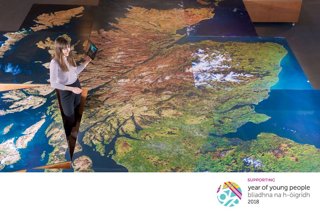 A young woman standing next to a large floor map of Scotland with the Year of Young People logo