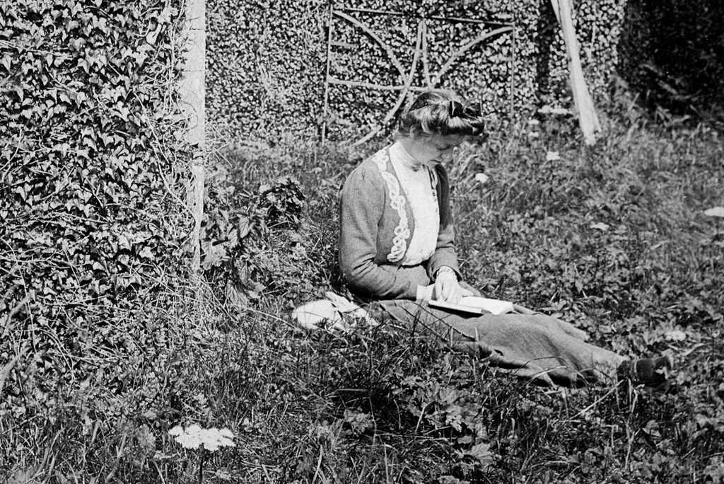 woman with hair in a bun and victorian clothes sites in long grass bent over a book