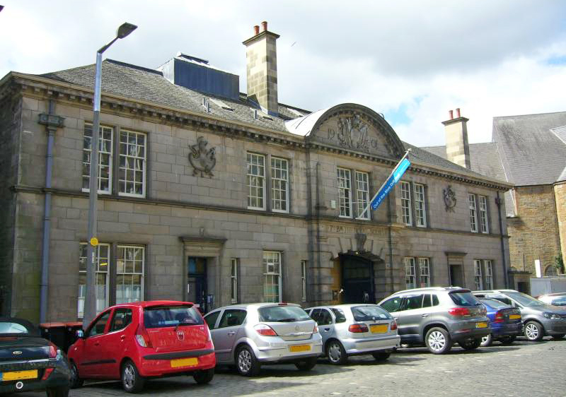 old fashioned drill hall building with cars parked outside the front and blue flag above main entrance