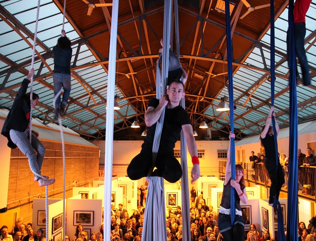 seven gymnasts in different positions on ropes and long pieces of material hanging from a ceiling with a large crowd below them looking up