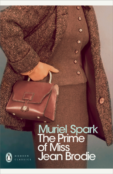 book cover showing a woman from shoulder to knee dressed in brown tweed suit and coat and carrying a brown handbag