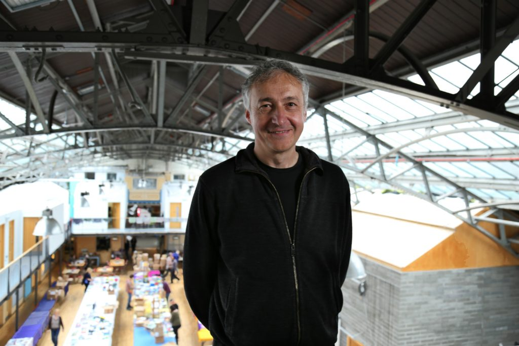 man smiles at camera from position of height with community hall visible behind him