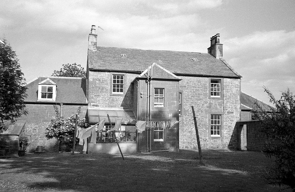black and white photo of a house with a washing line in front of it
