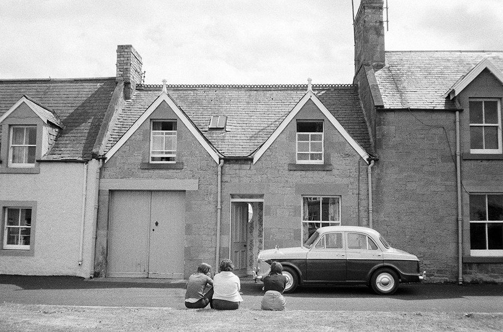 two people sit facing away from the camera towards a house with a car parked outside
