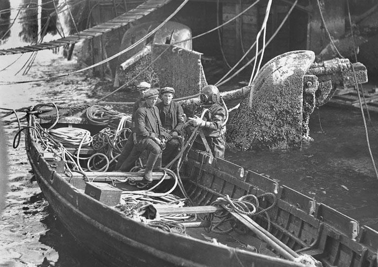 black and white image of divers in a boat
