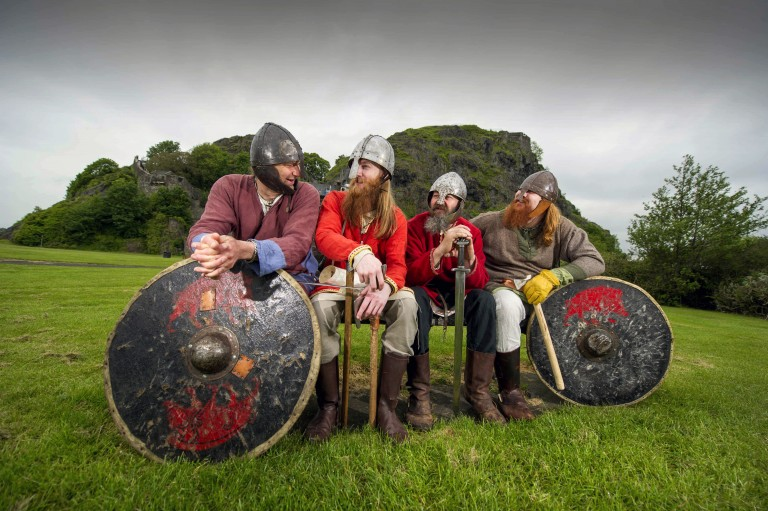four men in viking outfits sit in a row talking to each other. They are holding shields and swords